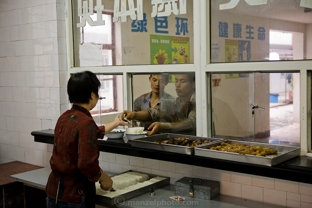 Workers buy food from a company cafeteria at a construction site in Shanghai, China. In China, migrant laborers often live directly on the job-site grounds of big construction projects and work 12-hour shifts, seven days a week. Alcohol is only tolerated in the company cafeteria after dinner.
