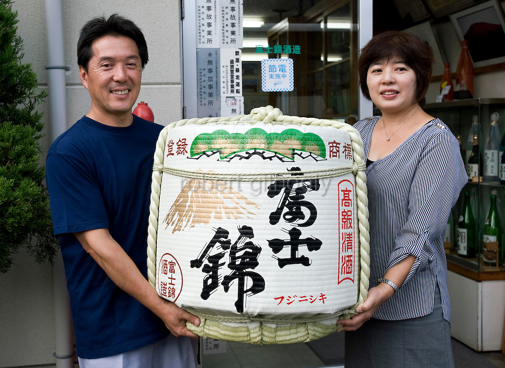Shinichi Sei, president of Fuji-nishiki Sake Brewery, and his wife Tomoko stand with a cask of the company's sake at the brewery in Fujinomiya, Shizuoka Prefecture Japan on 02 Oct. 2012.  Photographer: Robert Gilhooly