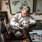 Local artisan Kinh Van Le, a master of traditional Hue silk embroidery, writes at his desk on his store in Hue, Vietnam. Some of his work hangs on the wall in the background.
