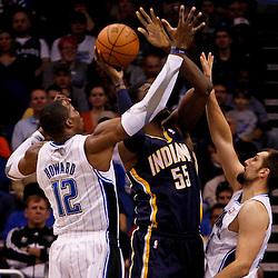 March 11, 2012; Orlando, FL, USA; Indiana Pacers center Roy Hibbert (55) is defended by Orlando Magic center Dwight Howard (12) and power forward Ryan Anderson (33) during the first quarter of a game at  Amway Center.   Mandatory Credit: Derick E. Hingle-US PRESSWIRE