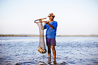 A fisherman holds up his daily catch on the river in Panjim, India.