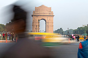 Traffic and pedestrians pass in front of India Gate in New Delhi, India.