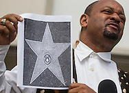 Najee Ali holds a picture with a star of Bill Cosby during a news conference on July 9, 2015 in Los Angeles, California. A coalition of black civil-rights advocates calls onto the Hollywood Chamber of Commerce President Leron Gubler to remove Bill Cosby's star on the Hollywood Walk of Fame. (Photo by Ringo Chiu/PHOTOFORMULA.com)