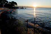 View of Opatija in early morning light, looking toward Lady With Seagull statue, with concrete ocean-front and steps in foreground. Rising sun reflecting off water. Opatija, Croatia
