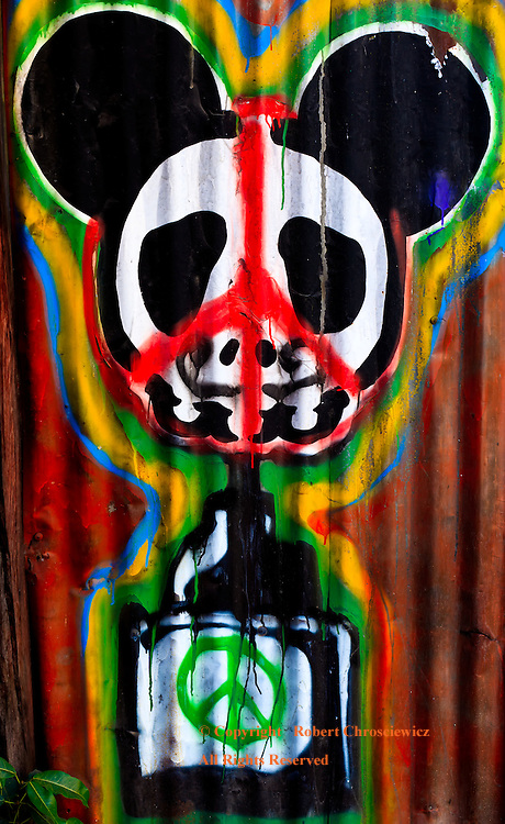 Multi coloured graffiti, emblazoned on a sheet metal wall, depicts an inkwell and a mouse head both covered with peace symbols, in Chiang Mai Thailand.<br />