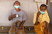 03 MARCH 2104 - MAE KASA, TAK, THAILAND:  A patient swallows some of the pills he has to take every day for treatment of tuberculosis at the Sanatorium Center for Border Communities in Mae Kasa, about 30 minutes north of Mae Sot, Thailand. The monk sitting next to him was waiting for his pills. The Sanatorium provides treatment and housing for people with tuberculosis in an isolated setting for about 68 patients, all Burmese. The clinic is operated by the Shoklo Malaria Research Unit and works with several other NGOs that assist Burmese people in Thailand. Reforms in Myanmar have alllowed NGOs to operate in Myanmar, as a result many NGOs are shifting resources to operations in Myanmar, leaving Burmese migrants and refugees in Thailand vulnerable. Funding cuts could jeopardize programs at the clinic. TB is a serious health challenge in Burma, which has one of the highest rates of TB in the world. The TB rate in Thailand is ¼ to ⅕ the rate in Burma.        PHOTO BY JACK KURTZ