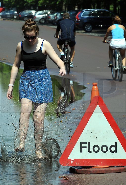 © Licensed to London News Pictures. 18/07/2014<br /> Teenager,  Sarah Mary (age 15) from Bromley cooling off in the flood water from  last nights storms in Greenwich Park,Greenwich,London today (18.07.2014)<br /> People enjoying the heatwave weather at Greenwich Park,Greenwich,London.<br /> (Byline:Grant Falvey/LNP)