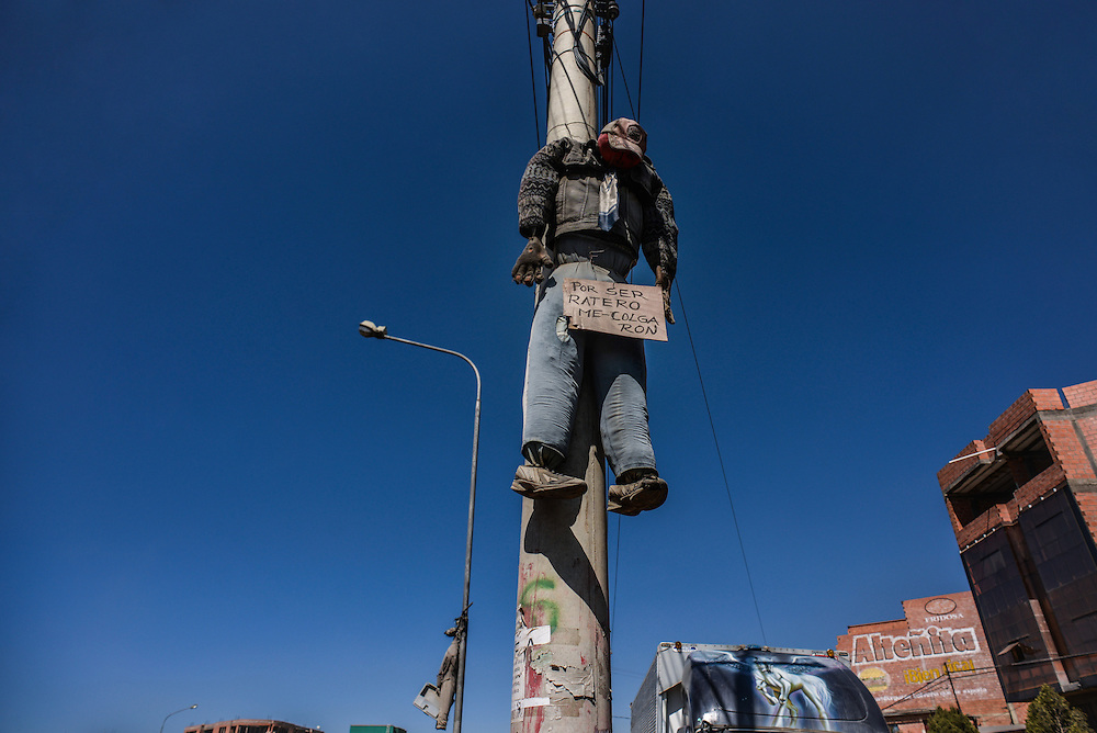 "Life-sized stuffed dolls hang from the electric polls across El Alto, signifying a threat. This particluar one holds a sign that says in Spanish, ""I was hung for being a thief"".  Photo by Meridith Kohut for The New York Times"