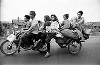 South Vietnamese family with all their goods seen fleeing the city of Xuan Loc on a scooter as it falls to the North Vietnamese army during the final months of the Vietnamese war. April 1975.Photograph by Terry Fincher