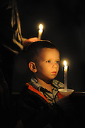 A boy holds a candle during the Easter Vigil service. (Sam Lucero photo)