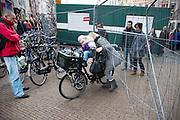 Mensen kruipen door een hek in de binnenstad van Utrecht. Het hek is geplaatst voor werkzaamheden aan de werfkade, maar het winkelend publiek trekt zich er weinig van aan.<br /> <br /> People are crawling with a bike through a fence in the center of Utrecht. The fence is to protect the construction area, but the public is ignoring it.