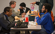 """Bus drivers coming in from their morning routes enjoy a free breakfast served by transportation staff at the Northwest bus yard as part of the """"Love the Bus"""" month celebration, February 13, 2014."""