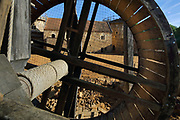 Lifting gear or squirrel cage with double drum (one drum viewed from the other) and behind, the North Range or Logis Seigneurial, completed 2010, and Great Tower or Tour Maitresse (right), at the Chateau de Guedelon, a castle built since 1997 using only medieval materials and processes, photographed in 2017, in Treigny, Yonne, Burgundy, France. The Guedelon project was begun in 1997 by Michel Guyot, owner of the nearby Chateau de Saint-Fargeau, with architect Jacques Moulin. It is an educational and scientific project with the aim of understanding medieval building techniques and the chateau should be completed in the 2020s. Picture by Manuel Cohen