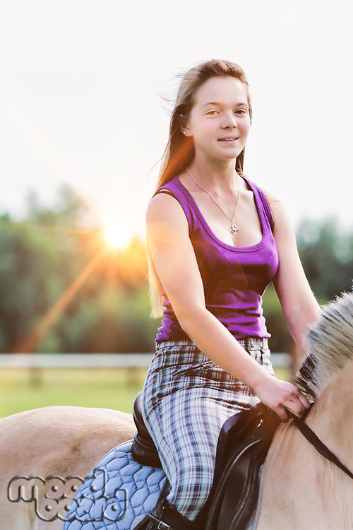 Portrait of young attractive woman riding horse in ranch