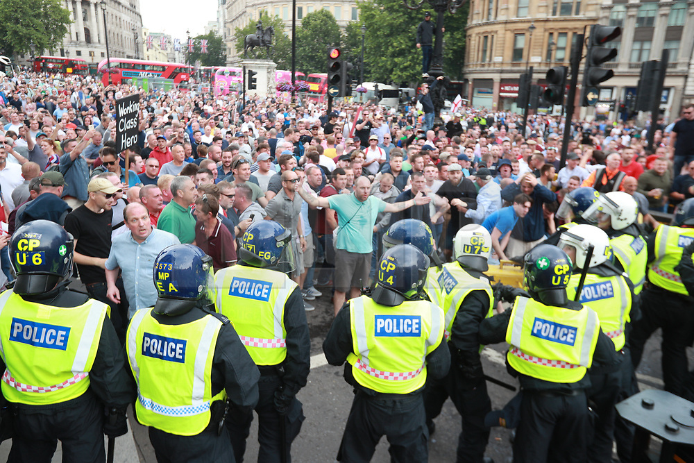 © Licensed to London News Pictures. 09/06/2018. London, UK. Protesters clash with police by Trafalgar Square. Thousands of supporters of EDL founder Tommy Robinson ( real name Stephen Yaxley-Lennon ) demonstrate in Westminster after Robinson was convicted of Contempt of Court . Robinson was already serving a suspended sentence for Contempt of Court over a similar incident , when he was convicted on Friday 25th May 2018 . Photo credit: Joel Goodman/LNP