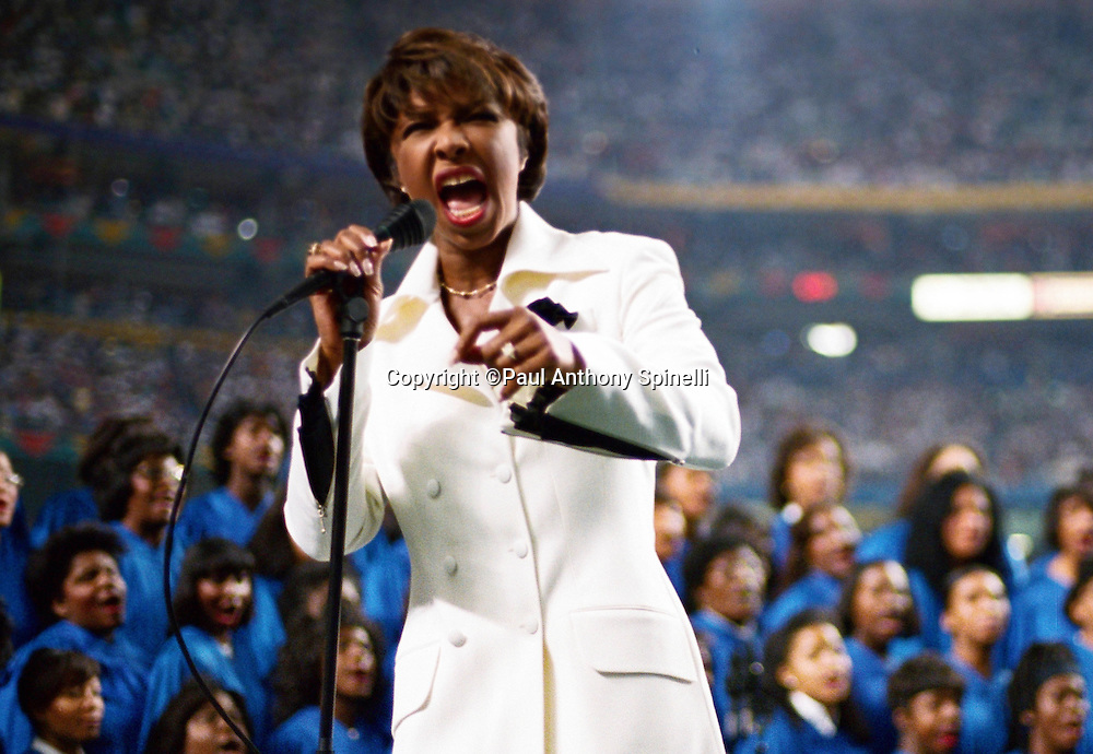 Singer Natalie Cole sings the National Anthem as part of the pregame show while backed up by the Atlanta University Center Choir before the Dallas Cowboys Super Bowl XXVIII NFL football game against the Buffalo Bills on Jan. 30, 1994 in Atlanta. The Cowboys won the game 30-13. (©Paul Anthony Spinelli)