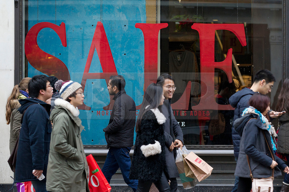 © Licensed to London News Pictures. 26/12/2013. London, UK. Shoppers pass a sale sign as they search for bargains on Regent Street during the Boxing Day sales in London today (26/12/2013). Photo credit: Matt Cetti-Roberts/LNP