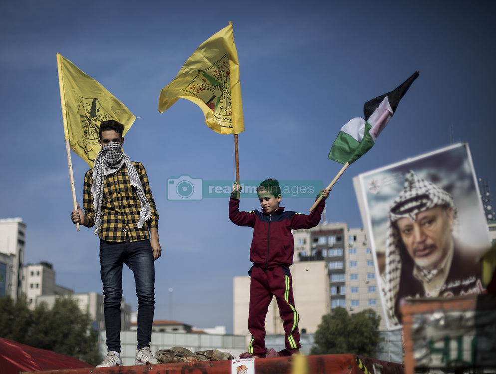 November 20, 2018 - Gaza City, The Gaza Strip, Palestine - Supporters of Fatah movement's former security chief and exiled Palestinian politician Mohammed Dahlan seen holding flags during a gathering held for the 14th anniversary of Yasser Arafat's death in Gaza city. Yasser Arafat died at 75 years old in a French hospital on November 11th, 2004, while Palestinians accused Israel of having poisoned him. (Credit Image: © Mahmoud Issa/SOPA Images via ZUMA Wire)