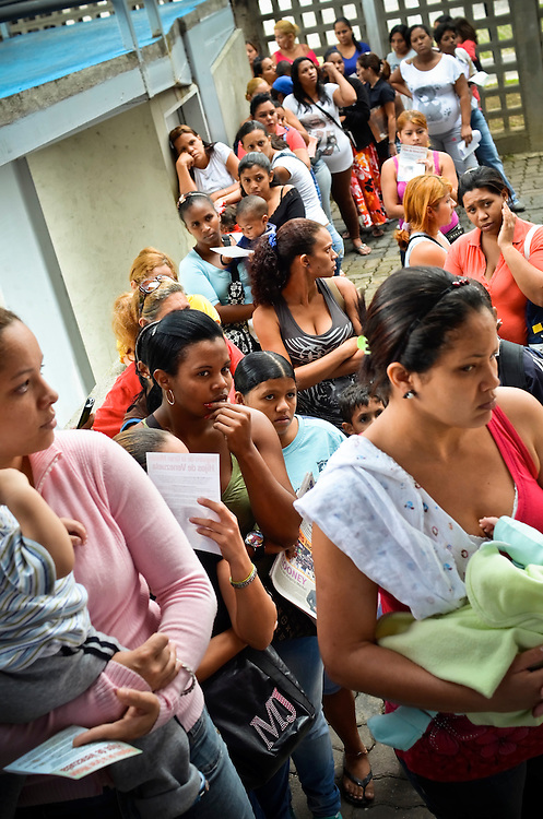 Women wait in line to register for a controversial government program that gives teenage mothers $100 USD a month per child. Opponents feel like the program encourages young girls who live in poverty to get pregnant. Venezuela has the highest rate of teenage pregnancies in Latin America.  26 percent of babies are born to underage mothers.