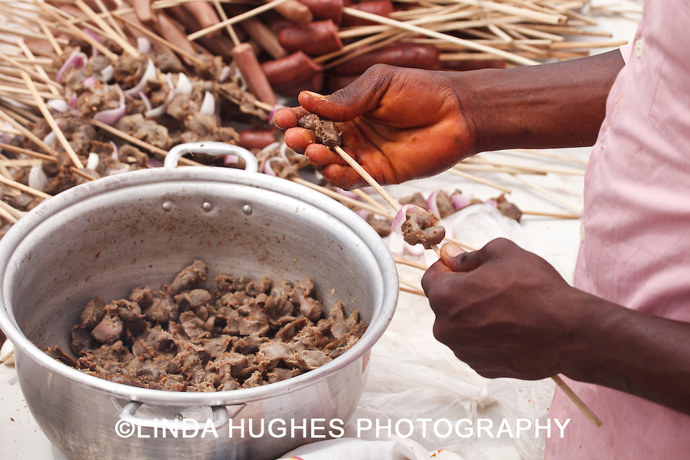 African Chef Threading Skewers in Ghana West Africa