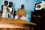 HIV/AIDS counselor Kevin Kouassi Gallet meets with members of the Djaha family in their home in Dimbokro, Cote d'Ivoire on Friday June 19, 2009. At left is Solange Djaha Ahou, 8, and at right her father Barthelemy Djaha N'Gueran. Both are HIV-positive.