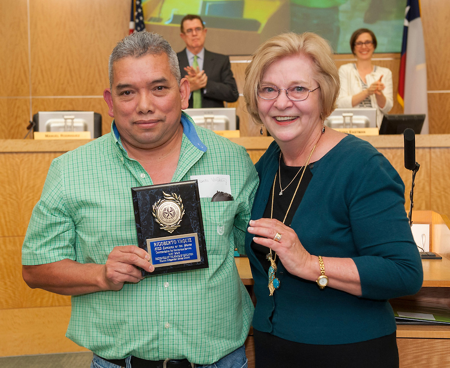 Rigoberto Vaquiz, left, receives an Employee of the Month award from Travis Elementary principal Susan Walker, right, during the monthly meeting of the Houston ISD Board of Trustees' meeting, April 11, 2013.