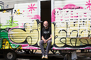 Gavin Turk, artist, photographed with a caravan (not his artwork) on wasteland near his East London studio, UK