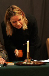 © under license to London News Pictures.  13/12/2010..Auctioneer, Rector Becky Bevan takes bids while keeping an eye on the nail at the age-old tradition of a candle auction. The auction, held every three years, is where people bid to lease a local meadow while a candle containing a horse-nail burns...The person with the bid when the nail drops out of the specially-made tallow candle is declared the winner...The event, which originates from the early 1800s, was held at Aldermaston Parish Hall, Berkshire,with the local vicar as the auctioneer. Church wardens, in-keeping with tradition, are given pipes, although they were not allowed to light them...Picture credit should read: Rebecca Mckevitt/London News Pictures