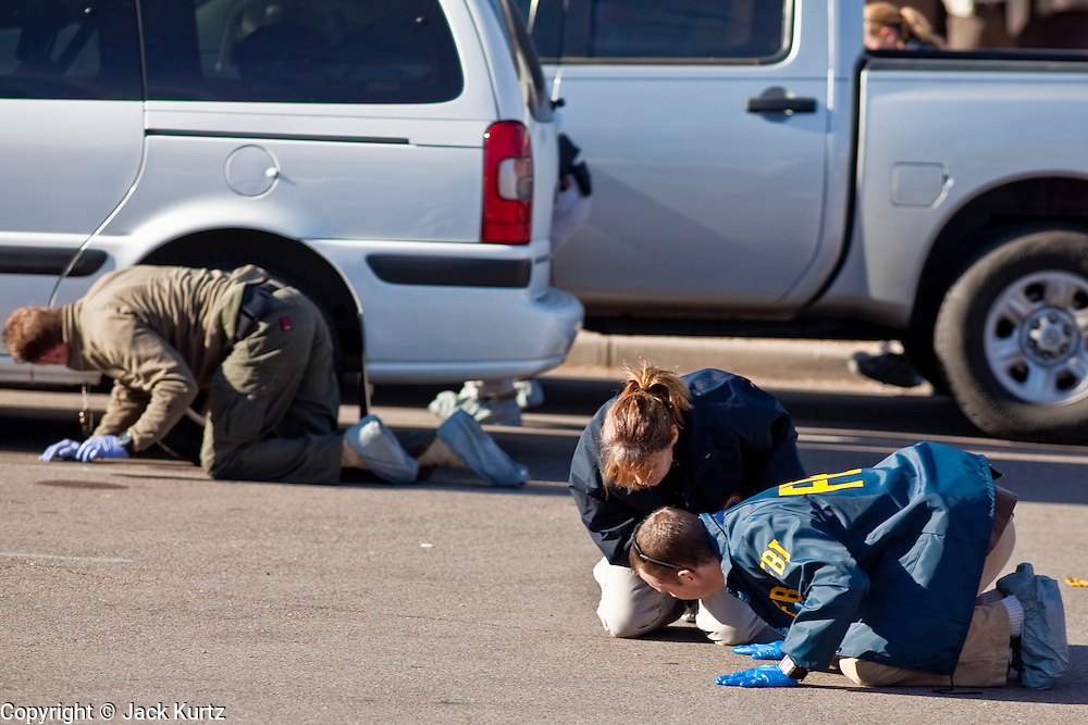 tucsonshooting - 10 JANUARY 2011 - TUCSON, AZ: FBI agents and Tucson area law enforcement officers scour the parking lot of the Safeway at Oracle and Ina Roads in Tucson looking for evidence Monday. Two days after a mass shooting at the Safeway, the grocery store is closed the parking lot a scene of intense law enforcement activity.   ARIZONA REPUBLIC PHOTO BY JACK KURTZ..Gabrielle Giffords shooting