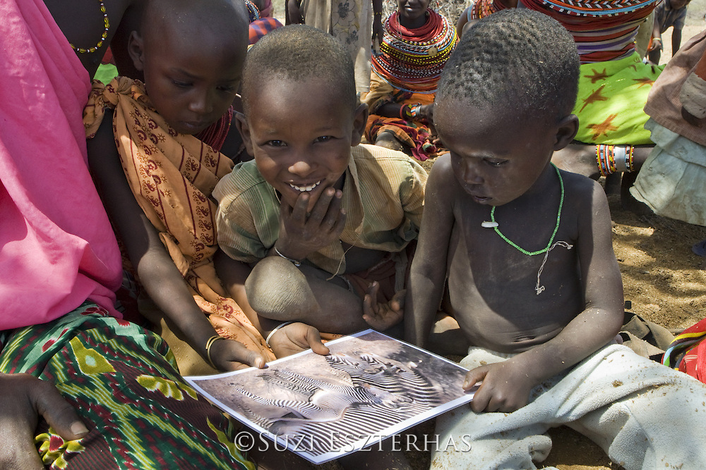 Grevy's Zebra Community Education in Laresoro Village<br /> Jalango Lekureiya (Grevy's Zebra Scout) eduates Samburu villagers about Grevy's zebras<br /> Near Kalama Conservancy, Northern Kenya, East Africa