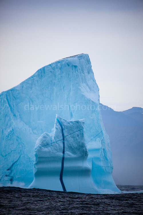 """An iceberg with a vertical line of dense blue ice running through from top to bottom, at the mouth of Kangderluqussuaq Fjord, East Greenland, 2009 This mage can be licensed via Millennium Images. Contact me for more details, or email mail@milim.com For giclée prints, contact me, or click """"add to cart"""" to some standard print options."""