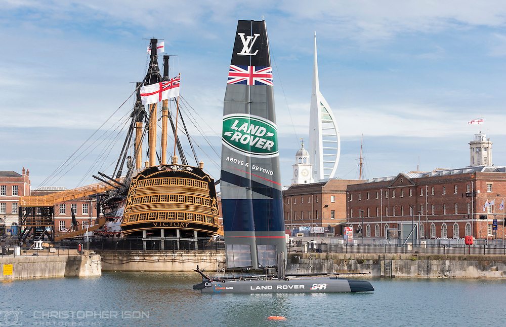 Sir Ben Ainslie's AC45 foiling catamaran is moored beside Admiral Lord Nelson's flagship, HMS Victory at the Historic Dockyard in Portsmouth on the first evening of the America's Cup World Series which runs until Sunday. <br /> The world's oldest sporting trophy has not been contested in British waters until now.<br /> Ainslie's team, Land Rover BAR, hope to wrestle it back from the current holders Oracle Team USA.<br /> Picture date: Thursday July 23, 2015.<br /> Photograph by Christopher Ison &copy;<br /> 07544044177<br /> chris@christopherison.com<br /> www.christopherison.com