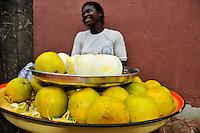 Nigeria - Female fruit vendor selling ready to peel oranges