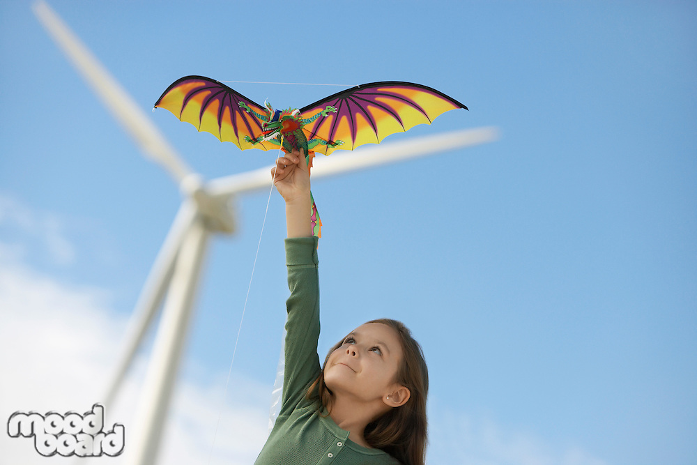 Girl (5-6) playing with kite at wind farm