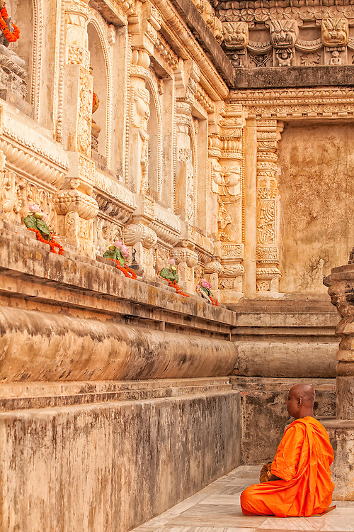 Buddhist monk meditating at the Mahabodhi Temple, the place of the Buddha's enlightenment in Bodhgaya India.