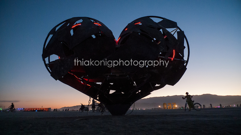 Near silloette of iron heart sculpture at dawn, Black Rock desert, Burning Man Festival.