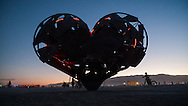 Near silloette of iron heart sculpture at dawn, Black Rock desert, Burning Man Festival.