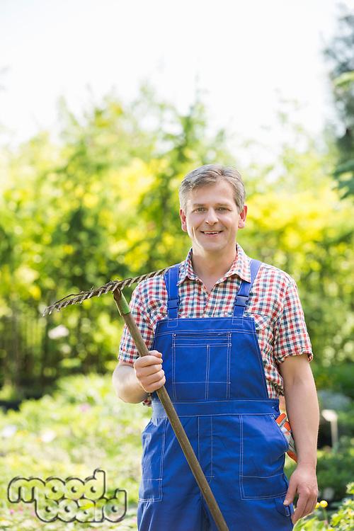 Portrait of confident gardener holding rake in plant nursery