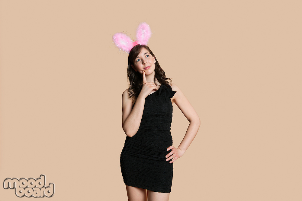 Thoughtful beautiful young woman with rabbit ears looking away over colored background