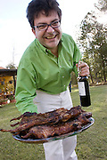 Pablo Corral Vega with a platter of roasted cui (guinea pigs) and a bottle of wine at a party at his farm house in Ecuador.