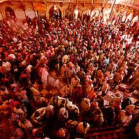 People gather inside the temple premises for the celebration. Braj ki Holi