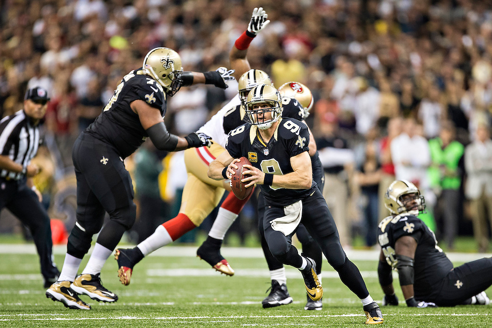 NEW ORLEANS, LA - NOVEMBER 17:  Drew Brees #9 of the New Orleans Saints scrambles with the ball against the San Francisco 49ers at Mercedes-Benz Superdome on November 17, 2013 in New Orleans, Louisiana.  The Saints defeated the 49ers 23-20.  (Photo by Wesley Hitt/Getty Images) *** Local Caption *** Drew Brees