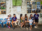 27 AUGUST 2016 - BANGKOK, THAILAND: Residents of the Pom Mahakan slum wait for a community luncheon to start. The Pom Mahakan community is known for fireworks, fighting cocks and bird cages. Mahakan Fort was built in 1783 during the reign of Siamese King Rama I. It was one of 14 fortresses designed to protect Bangkok from foreign invaders. Only two of the forts are still standing, the others have been torn down. A community developed in the fort when people started building houses and moving into it during the reign of King Rama V (1868-1910). The land was expropriated by Bangkok city government in 1992, but the people living in the fort refused to move. In 2004 courts ruled against the residents and said the city could evict them. The city vowed to start the evictions on Sept 3, 2016, but this week Thai Prime Minister Gen. Prayuth Chan-O-Cha, sided with the residents of the fort and said they should be allowed to stay. Residents are hopeful that the city will accede to the wishes of the Prime Minister and let them stay.       PHOTO BY JACK KURTZ