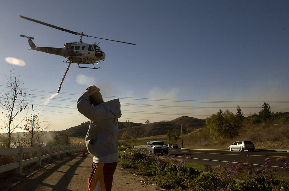 Moorpark Country Club Estates resident Starr Cole holds onto her hat as a CDF helicopter takes off after refueling with water at a pond on the golf course while fighting the Shekell Fire in on Sunday.