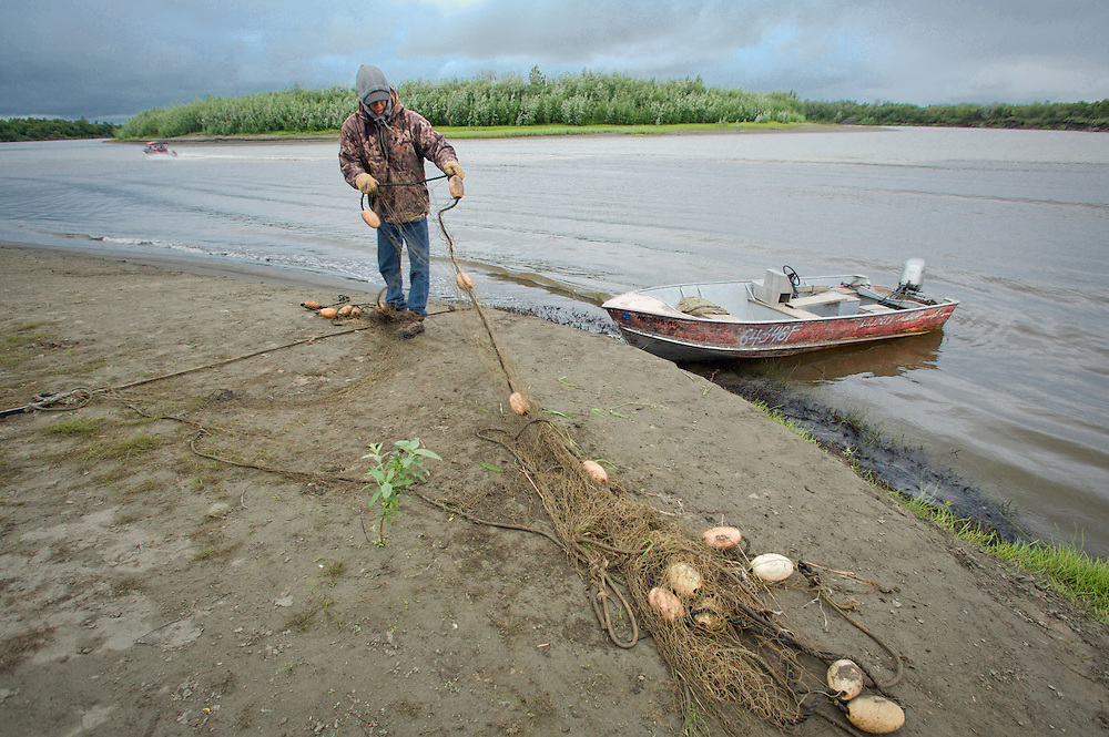Henry Spein prepares his set net for subsistence fishing at fish camp near Kwethluk, Alaska. With both ends anchored, the top of the set net is held by floats while the net sinks to the bottom. From his skiff Spein will pull fish from the nets later in the day.