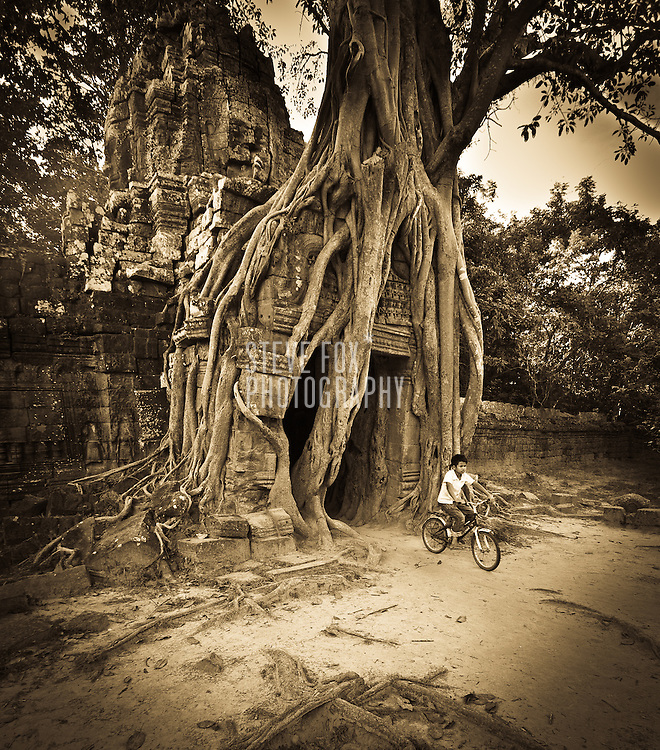 Boy cyclist emerges from Ta Som, Siem Reap, Cambodia