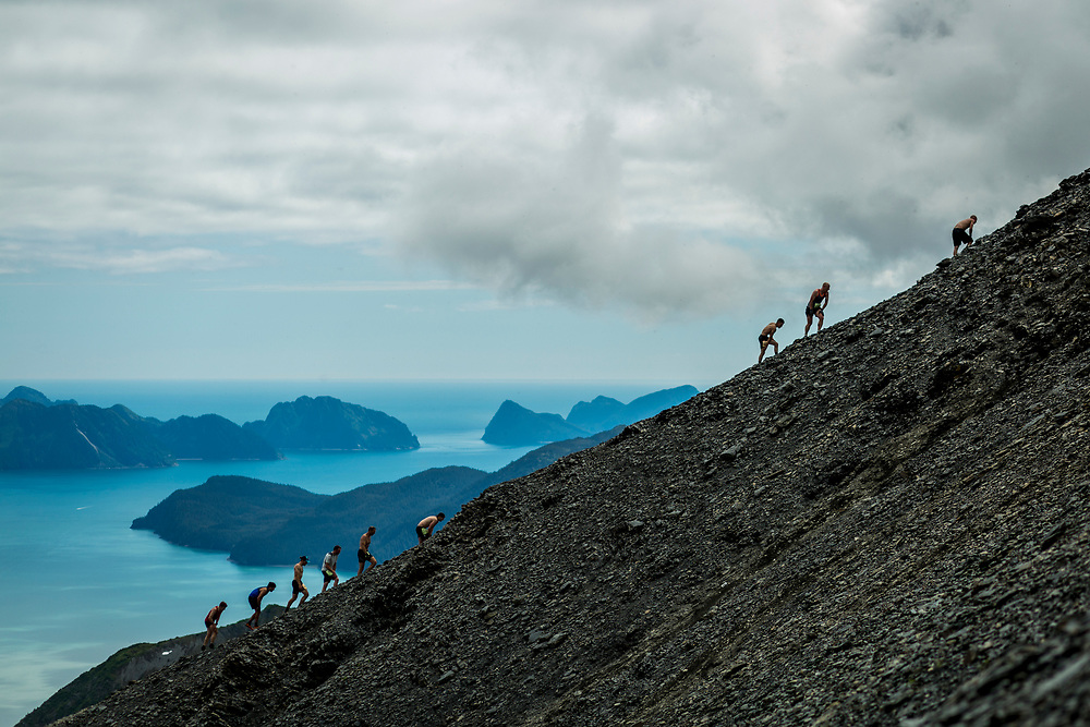 Men's competitors ascend the mountain with Resurrection Bay seen in the distance. The five-kilometre race ascends nearly 1000 metres up Mount Marathon before plunging back to sea level.