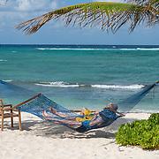 Couple enjoying vacation time on hammock. Wyndham Reef Resort. East End. Grand Cayman Island.