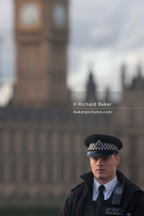 Police officer stands guard opposite the Houses of Parliament, after our people were killed (including the attacker) and 20 injured during a terrorist attack on Westminster Bridge and outside the Houses of Parliament, on 22nd March 2017, in central London, England. Parliament was in session and all MPs and staff and visitors were in lock-down while outside, the public and traffic were kept away from the area of Westminster Bridge and parliament Square, the scenes of the attack. It is believed a lone man crashed his car into pedestrians then, armed with a knife tried to enter Parliament, stabbing and killing a police officer at parliament's main gates.