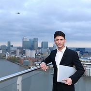 Young businessman on balcony with laptop and view of skyscrapers and Canary Wharf , London. A helicopter hovers overhead.<br />